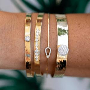 4 gold and diamond bracelets on wrist