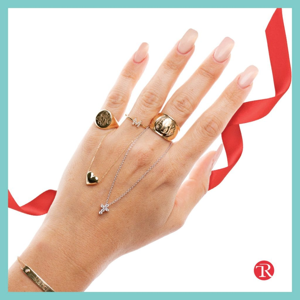 Picture of hand with ribbon in the background. Hand is modeling the express yourself jewelry trend jewelry. Hand has a ring on three fingers and a bracelet on the wrist. A heart necklace hangs from the ring finger and a cross necklace hangs from the middle finger.