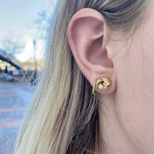 gold knot earring and gold and diamond hoop earring on model