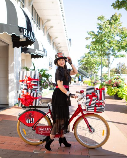 marci bailey on bailey bike with holiday packages in front of cameron village store