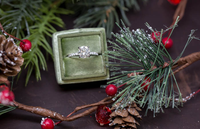 engagement ring in green velvet ring box next to a christmass tree, pinecone, and red berries