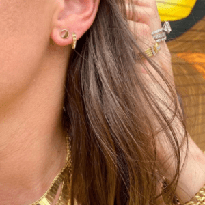 2 gold earrings on model with gold necklaces, rings and bracelets