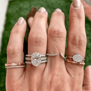 gold, silver and diamond rings on hand with green background