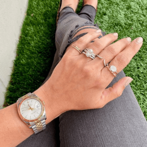 gold and silver watch and gold, silver and diamond rings on model