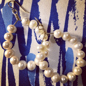 pearl hoop earrings on blue and white background