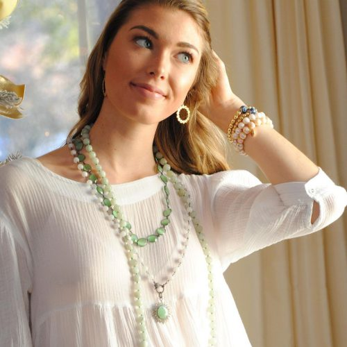 Girl wearing Wendy Perry jewelry smiles and looks off to the right.
