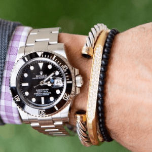 men's silver watch, silver and gold bracelet, gold and diamond bracelet, and black beaded bracelet on model