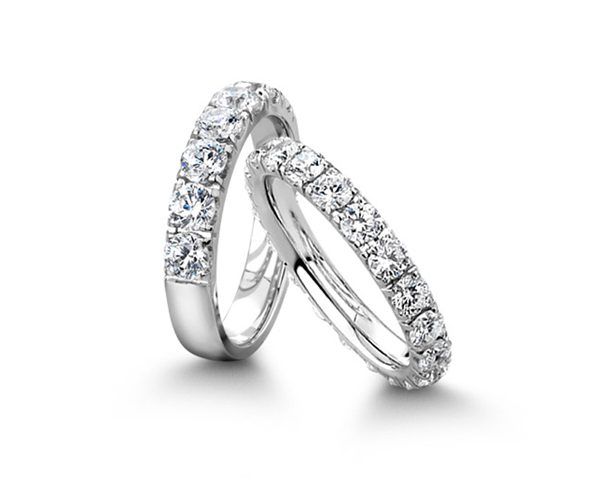 Two diamond and white gold wedding rings on white background.