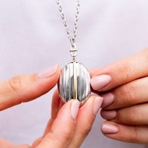closeup of woman holding silver and gold stripe locket