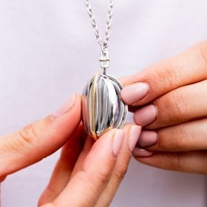 woman opening silver and gold stripe locket