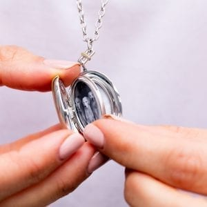 woman holding open locket with black and white pictures of dogs