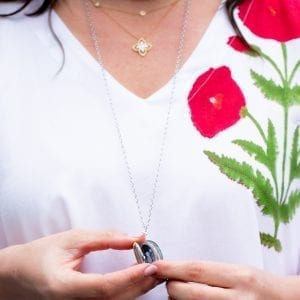 woman in white and floral dress opening locket