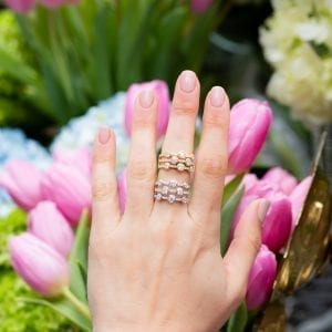 womans hand with two 3-row bezel set diamond rings stacked on middle finger in front of pink tulips and blue hydrangeas