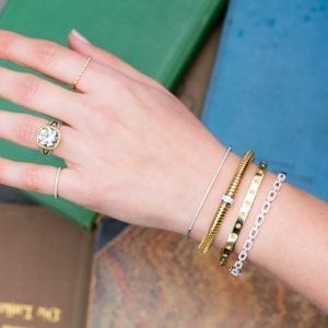 womans hand & wrist over pile of books wearing four diamond and gold bracelets
