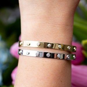 white gold and yellow gold bezel set diamond cuff bracelets on woman's wrist