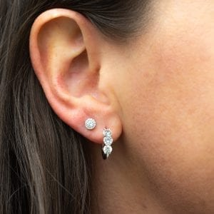 woman's ear with diamond halo stud and diamond huggie hoop earrings in 14kt white gold