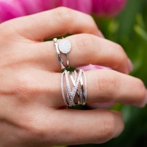 woman wearing three white gold and diamond rings