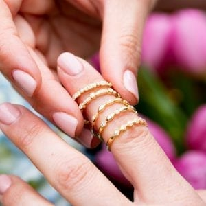 woman stacking 5 gold and diamond rings on finger over pink and blue flowers