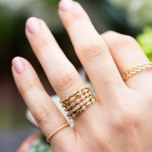 yellow gold and diamond ring stack on womands hand