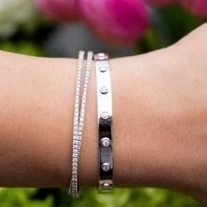 diamond flex crossover bangle and bezel set diamond bangle on woman's wrist in front of greenery & pink tulips