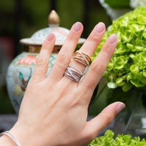 woman's hand with two crossover diamond band rings stacked on middle finger infront of plants & vase