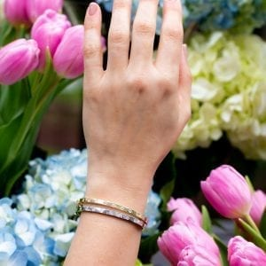 womans hand and wrist infront of blue and pink flowers wearing two bezel set diamond station bracelets