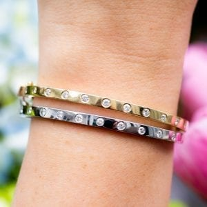 close up view of womans hand and wrist infront of blue and pink flowers wearing two bezel set diamond station bracelets