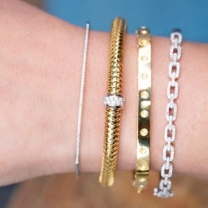 close up view of womans wrist wearing four diamond and gold bracelets