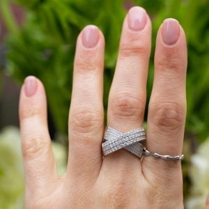 white gold and diamond crossover bridge ring on womans middle finger infront of greenery