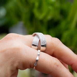 side view of womans finger showing a close up view of the crossover diamond bridge ring in 14kt white gold