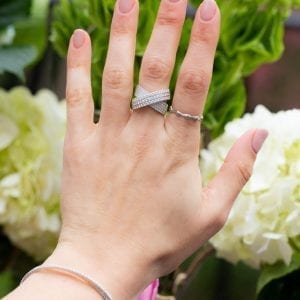 white gold and diamond crossover bridge ring on womans middle finger infront of greenery and flowers