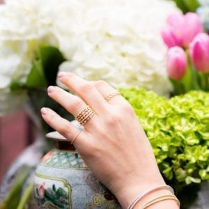 womans hand infront of vase and flowers wearing gold and diamond rings and bracelets