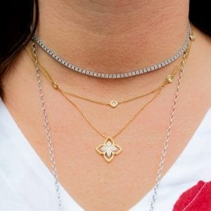 close up of woman wearing diamond and gold necklaces layered on neck