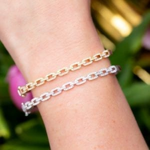 close up view of woman's wrist wearing two pave diamond link bracelets