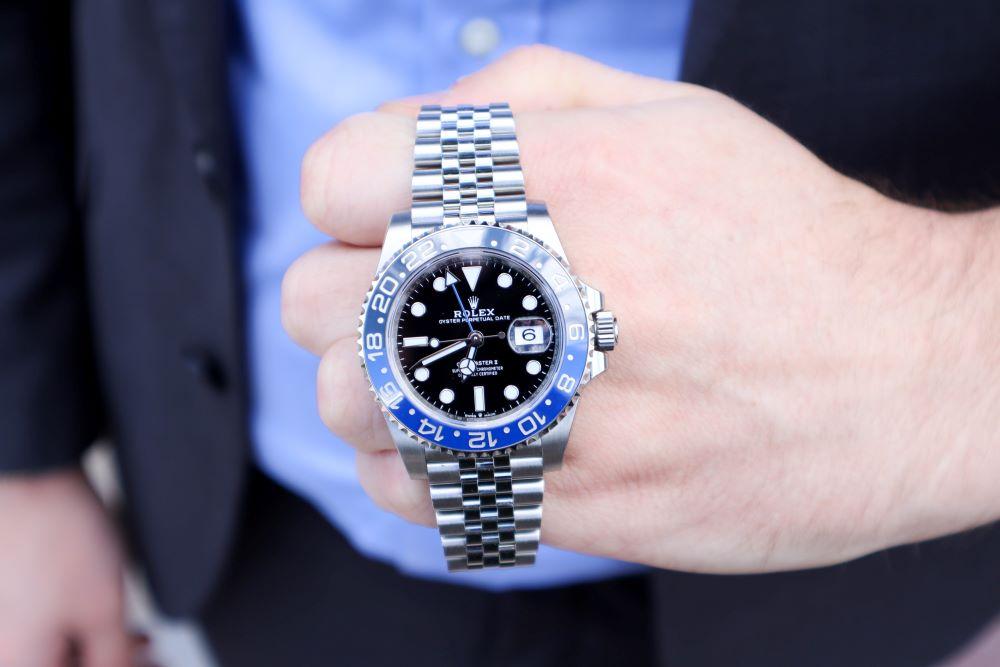 Rolex GMT Master II Batman on man's hand in dark suit